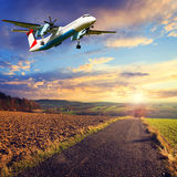 Sunset over road with plane Stock Photography