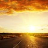 Sunset over road to horizon Stock Photo