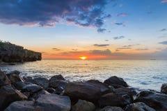 Sunset over rock beach over coastline Stock Photo