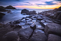 Sunset over rocks formation Giants Causeway, County Antrim, Northern Ireland, UK. Sunset over basalt rocks formation Giant`s Causeway, Port Ganny Bay and Great Royalty Free Stock Photo