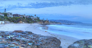 Sunset over the rocks at Shaws Cove. In Laguna Beach as water flows over the stone in HDR Stock Image