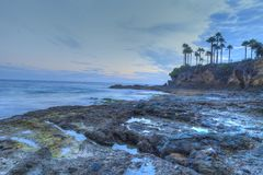 Sunset over the rocks at Shaws Cove. In Laguna Beach as water flows over the stone in HDR Stock Photography