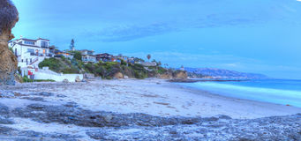 Sunset over the rocks at Shaws Cove. In Laguna Beach as water flows over the stone in HDR Royalty Free Stock Images