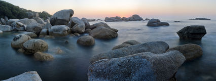 Sunset over rocky beach. Panoramic shot of a sunset over a rocky beach Royalty Free Stock Photography