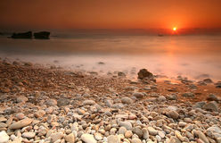 Sunset over rocky beach. Orange sunset over rocky beach and sea with blurred effect royalty free stock photo
