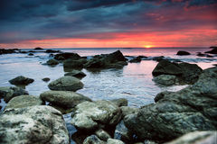 Sunset over rocky beach Stock Images