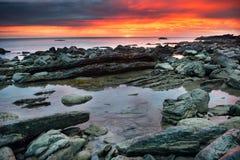 Sunset over rocky beach Stock Photos