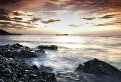 Sunset over rocky coast. Picturesque sunset and cloudscape over rocky coastline with silhouetted boat in background, Socotra or Soqotra island in Indian ocean Royalty Free Stock Images