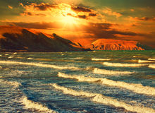 Sunset over rocky coast. In stormy weather Royalty Free Stock Photos