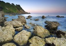 Sunset over rocky coastline Stock Images