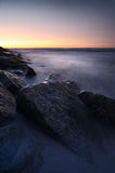Sunset over rocky coastline. Scenic view of sunset over rocky coastline with long exposure effect Stock Image