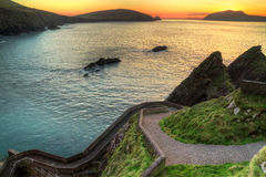 Sunset over rocky irish coast. Sunset over pathway leading to Dunquin Pier on Dingle Peninsula, Co.Kerry, Ireland - HDR Stock Images