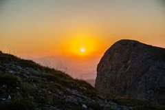 Sunset over the rocky ridge. The last rays of the sun shine from behind the rocky ridge and illuminate the sunset rays Royalty Free Stock Image