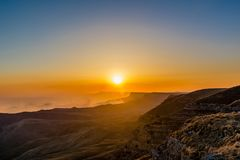 Sunset over the rocky ridge. The last rays of the sun shine from behind the rocky ridge and illuminate the sunset rays Royalty Free Stock Images