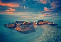 Sunset over rocky sea coast. Beautiful sunset over the rocky sea coast Royalty Free Stock Images