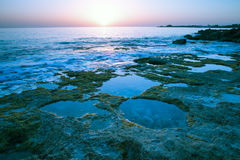 Sunset over the rocky shore of the Mediterranean Sea. Toned Stock Photo