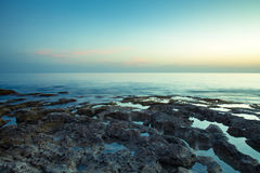 Sunset over the rocky shore of the Mediterranean Sea. Toned Royalty Free Stock Photography