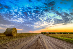 Sunset over rural road and hay bales Stock Images