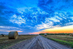 Sunset over rural road and hay bales Royalty Free Stock Photography