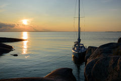 Sunset over sailboat moored long side a small rocky island Stock Images