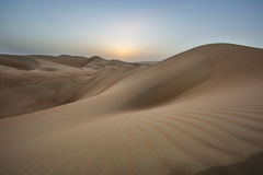 Sunset over sand dunes of Empty Quarter desert. Sunset over massive sand dunes of the Emty Quarter desert, covering large area in UAE, KSA and Oman Royalty Free Stock Images
