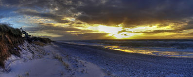 Sunset over sandy beach. Wide angle view of cloudscape and sunset over snow covered sandy beach Stock Images