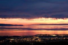 Sunset over Santa Barbara. Golden sunlight peeks through dark storm clouds over the Pacific ocean and the city lights of Santa Barbara, California Royalty Free Stock Image