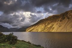Sunset over scenic mountain valley in Lake District,Cumbria,Uk. Sunset in mountain area.Sunlight painting rocky mountain slopes falling into lake during golden stock images