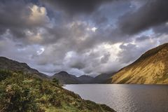 Sunset over scenic mountain valley in Lake District,Cumbria,Uk. Sunset in idyllic mountain valley with lake.Sunlight painting rocky mountain slopes falling into stock photography