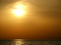 Sunset over the sea. Sunset over a calm sea on the background of the setting sun Stock Photo