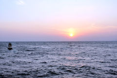 Sunset over sea. A background of a beautiful sunset over the sea,with a small boat.Photo taken is Sanya of China Stock Photography