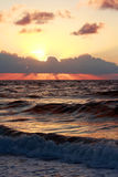 Sunset over sea. Scenic view of sunset behind cloudscape over sea with waves breaking in foreground Stock Image