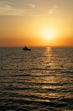 Sunset over the sea. Above the sea, the sky lit up the setting sun. Its rays are colored highlights on the waves of the sea. In the sea to the black silhouette Royalty Free Stock Photo