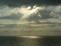 Sunset over the sea in bizarre clouds emitting a ray. In the sea falls a ray of sun, creating a sunny path or spot on the surface of the sea. Glowing clouds at Royalty Free Stock Photo