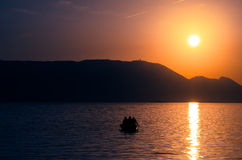 Sunset over sea and boat with men Stock Photo