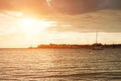 Sunset over the sea and city. Royalty Free Stock Images