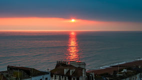 Sunset over sea at a coastal city. Warmish, reddish orange sunlight trace is reflected in the waters of seaside town at dawn Royalty Free Stock Photography