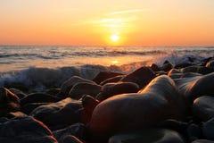 Sunset Over The Sea. Evening. Black sea seaside. Stones on the seashore with splashing waves and sunset Over The Sea background. Evening on the seashore. Black stock photos