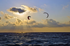 Sunset over the sea with kite surfers Royalty Free Stock Photo