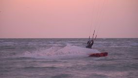 The man controls a training kite against the backdrop of sunset, slow-motion shooting. Sunset over the sea and a man in a suit for diving sails to the side stock video footage