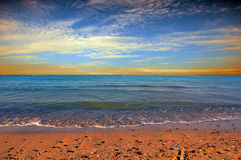 Sunset over sea with oncoming waves Royalty Free Stock Images