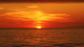 Sunset over sea and orange clouds Stock Image