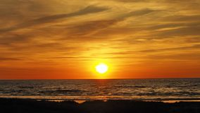 Sunset over sea and orange clouds Royalty Free Stock Image