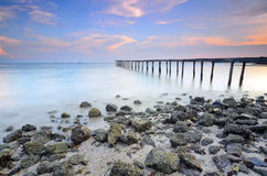 Sunset over the sea. Pier on the foreground Royalty Free Stock Photos