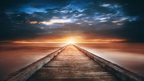 Sunset over the sea. Pier on the foreground Stock Image