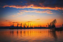 Sunset over sea port and industrial cranes, Varna Royalty Free Stock Photos