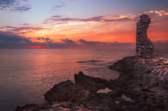 Sunset over the Sea and Rocky Coast with Ancient Ruins Stock Image