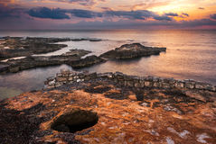 Sunset over the Sea and Rocky Coast with Ancient Ruins Stock Photography