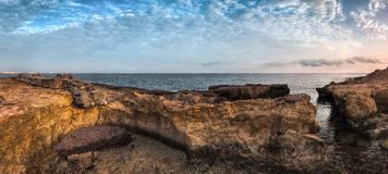 Sunset over the Sea and Rocky Coast Stock Images