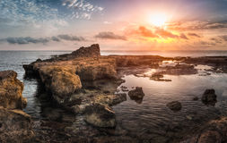 Sunset over the Sea and Rocky Coast Stock Image